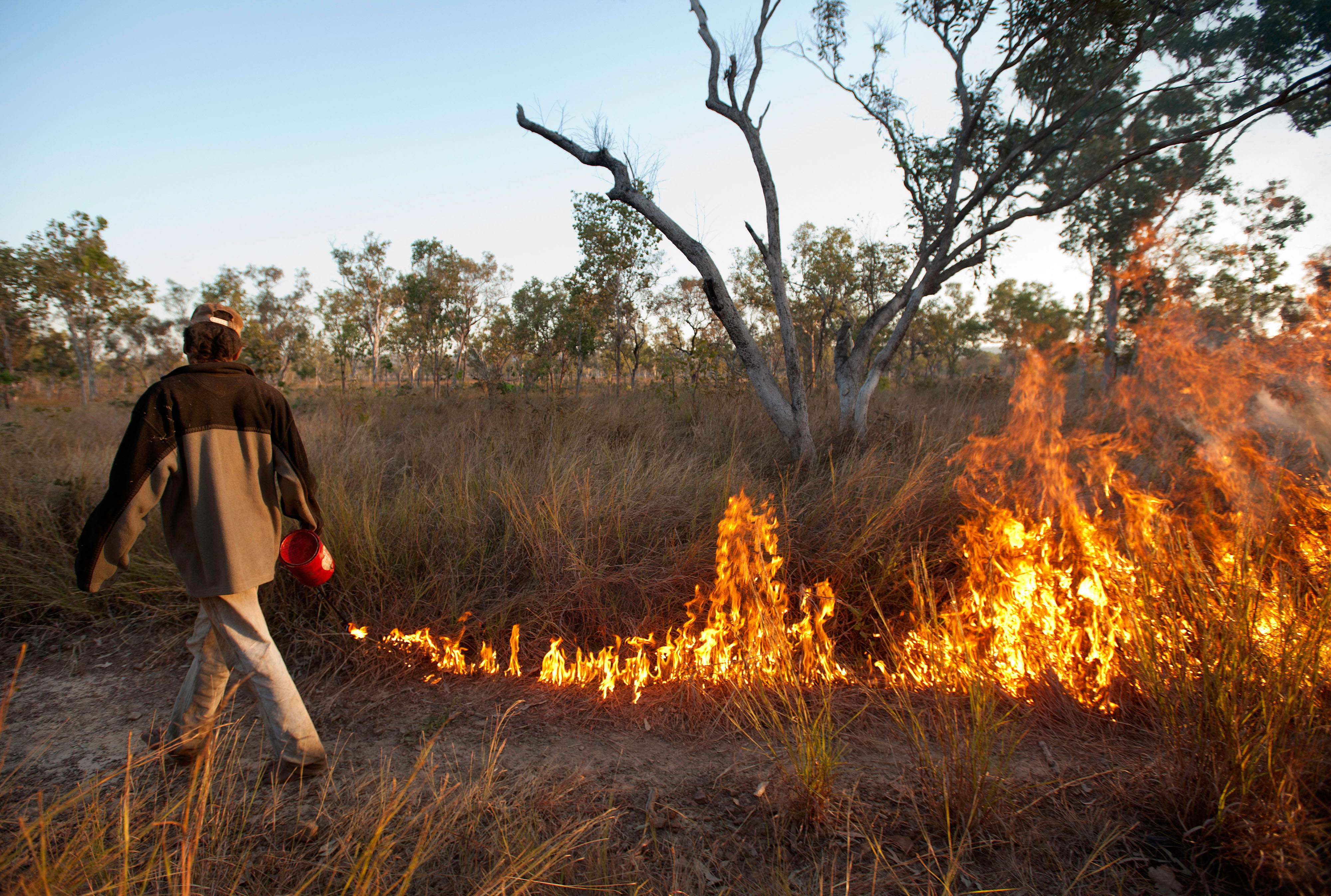 A man tending a controlled burn on a grassy area